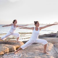 Two sisters are doing yoga exercises at the seashore of Mediterranean sea